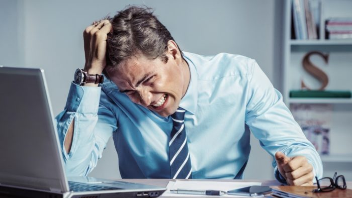 A businessman pulls his hair in frustration.