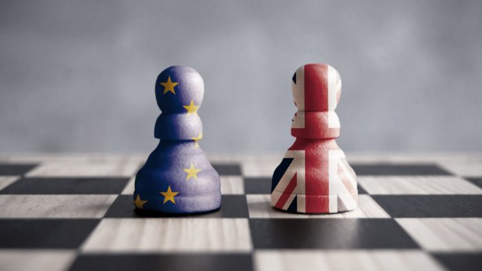Two chess pawns with UK and European flags.